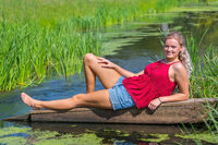 Young blond dutch woman lying above water in nature