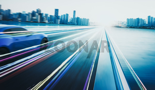 3D rendering of a brand-less blue sport car with light effect and motion blur . City skyline background . Sunset scene .