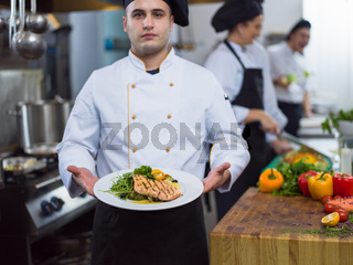 Chef holding dish of fried Salmon fish fillet