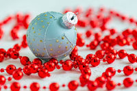 Silver Christmas ball and red beads.
