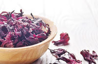 Closeup view at wooden bowl of dry hibiscus petals on white background