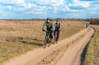 Cycling on the field road, two cyclists