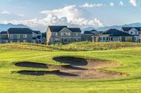 Bunker and fairway of a golf course with mountain and homes in the background