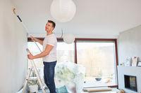 Mann als Heimwerker streicht eine Wand