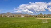 Panorama frame Soccer field and baseball field with view of mountain and cloudy blue sky