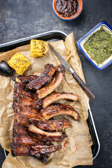 Barbecue spare ribs St Louis cut with hot honey chili marinade and chimichurri sauce as top view in a skillet