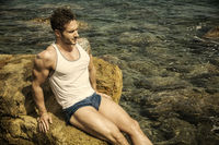 Handsome muscular man on the beach sitting on rocks