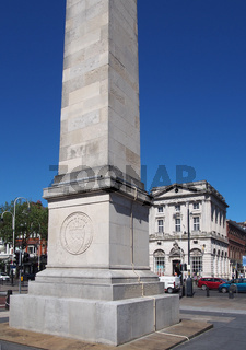 the war memorial in the town square at southport merseyside with surrounding buildings and traffic against a blue summer sky