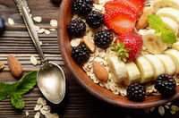 Flat lay top view at Fruit healthy muesli with banana strawberry almonds and blackberry in clay dish on wooden kitchen table