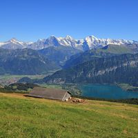 Azure blue Lake Thun, Bernese Oberland. Snow capped mountains Eiger, Monch and Jungfrau, view from M
