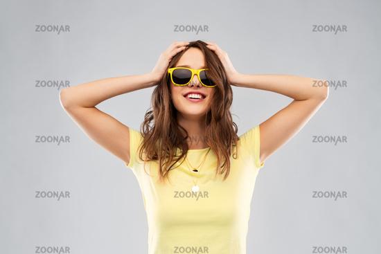 teenage girl in yellow sunglasses and t-shirt
