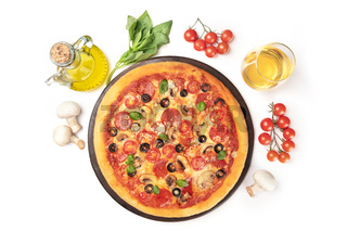 Pepperoni pizza with wine and ingredients, shot from the top on a white background with a place for text. Mushrooms, olive oil, basil, tomatoes around a pizza stone