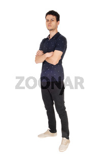 Tall young man standing with his arms crossed