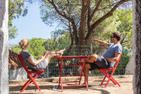 Couple on vacations resting in front of bungalow house at camping site in pure nature. Family vacation travel, holiday trip Sardigna, Italy