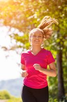 young woman jogging on sunny day at nature