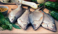 Fish and components for her preparation: vegetables, spices, parsley.