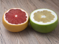 Halves of Green Sweetie and Red Grapefruit on wooden background. Close up view.