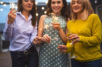 Group of partying girls with flutes with sparkling wine and bengal fire