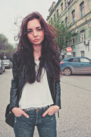 Sad girl in rip jeans and leaser jacket posing in the center of the street looking at camera
