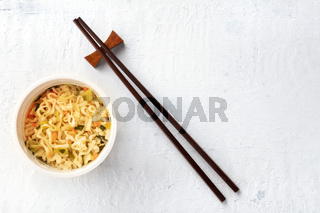 Plastic cup of instant ramen noodles, shot from above with chopsticks and a place for text