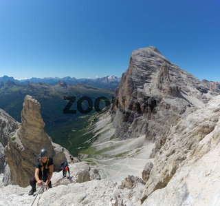 several mountain climbers on an exposed Via Ferrata in the Dolomites of Italy