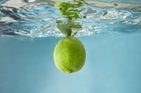 A whole lime with green leaves falls into the water on a blue background