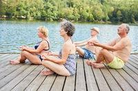 Senioren im Yogakurs meditieren am Badesee