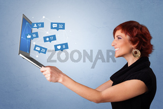 Woma holding laptop with social media notifications