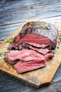 Traditional barbecue dry aged sliced roast beef steak with herbs as closeup on an old cutting board with copy space