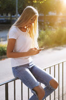 urban teenage girl using smartphone mobile on street