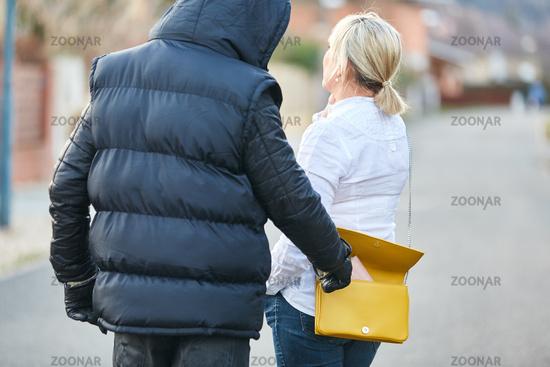 Taschendieb beim Stehlen von Brieftasche