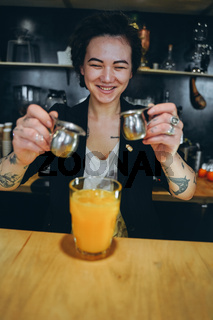 KIEV, UKRAINE - APRIL 14, 2019 A girl makes a orange coffee cocktail