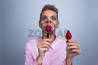 Woman with magnifying glass and strawberry