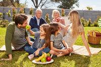 Familie mit Kindern und Großeltern beim Picknick