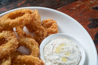 Fried calamari rings with dip sauce isolated on rustic wooden table
