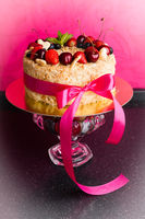 sponge cake with berries on pink