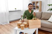 indian man checking takeaway food order at home