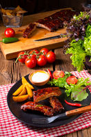 bbq spareribs on the plate with green salad and white sauce.