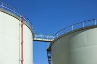 Fuel storage tanks with catwalk bridge against blue sky