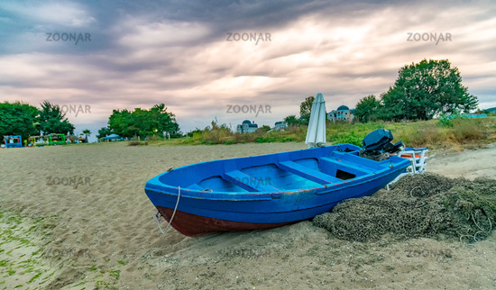 A blue boat and fishing net at sunset on a beach in Sunny Beach on the Black Sea coast of Bulgaria
