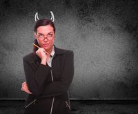 Devil Horns Drawn on Head of Red Faced Young Adult Woman with Pencil In Front of Grungy Wall with Copy Space