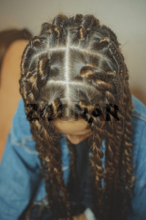 thin braids on the head in African style thick braids, dreadlocks, Senegalese braids, twists, mambo twists