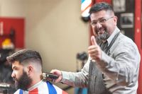 Portrait of a barber working while showing thumb up. Positive approval sign.