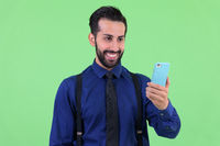 Young happy bearded Persian businessman using phone