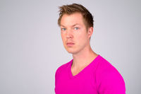 Face of young handsome man wearing purple shirt against white background