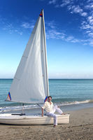 Cuba. A man on the blue sea next to a boat with a sail