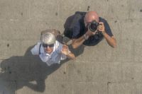 Mature couple is looking and photographing upwards. Top view.