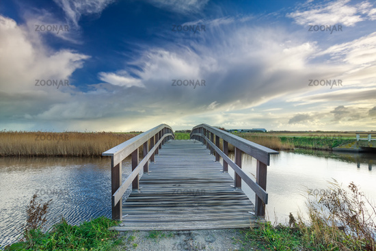 wooden bridge via river and blue sky