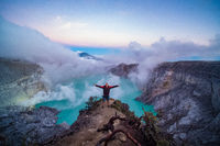 Man traveler standing on edge of crater Ijen volcano with colorful sky at morning