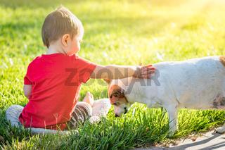 Cute Baby Boy Sitting In Grass Petting Dog